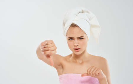 Woman with a towel on her head shoulders wet hair problems we face with skin