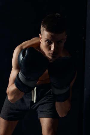 boxer in black gloves bent down on a dark background bodybuilder fitness workout