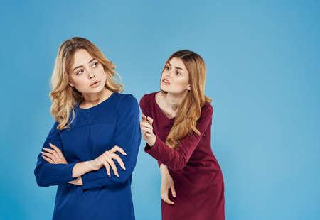 Elegant women in dresses communicating emotions blue background conflict