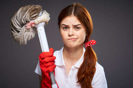 cleaning lady with disgruntled expression mop in hand cleaning rooms