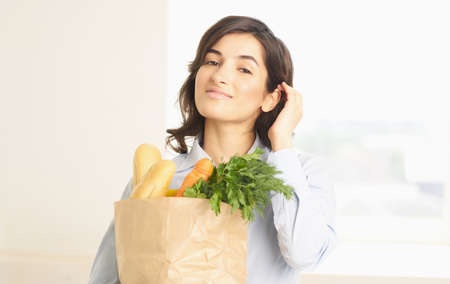 brunette with a package of groceries vegetables greens supermarket shopping