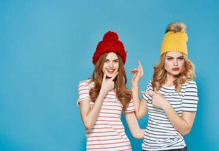 Women in multi-colored caps emotions discontent quarrel conflict blue background