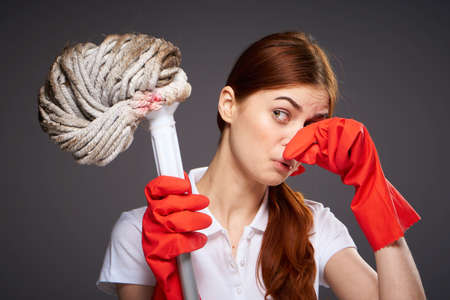 cleaning lady covers her nose with her fingers unpleasant smell mop in hand cleaning discontent