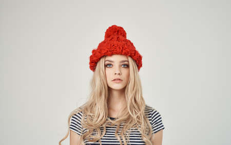 blonde woman in striped t-shirt and red hat portrait on light background cropped view