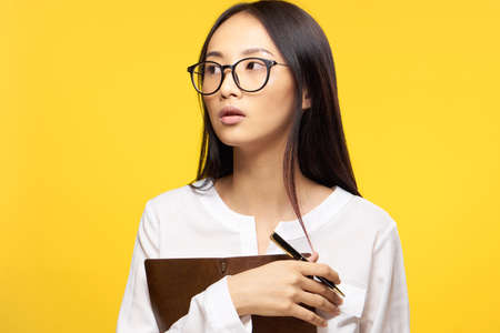 Business woman with notebook hands and pen office manager yellow background