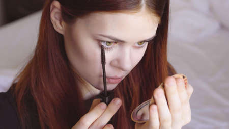 woman paints eyelashes with a mirror in hand self-care femininity