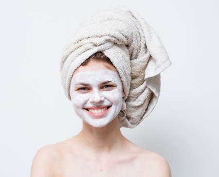 happy woman with white mask on her face shoulders clean skin towel on head