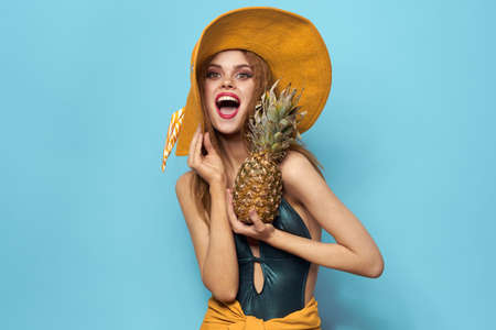 Cheerful woman beach hat exotic fruits swimsuit lifestyle blue background