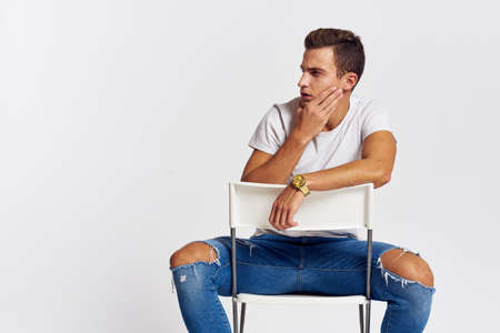 Man on a chair indoors torn jeans white t-shirt handsome face model light background
