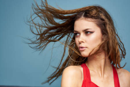 Beautiful woman with wavy hair bright makeup red t shirt lifestyle blue background model Foto de archivo