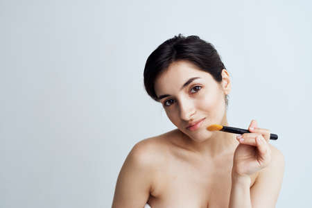 Pretty woman with naked shoulders applying makeup on face lifestyle