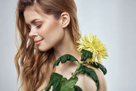 Portrait of a beautiful woman with a yellow flower on a light background charming smile model red hair Foto de archivo