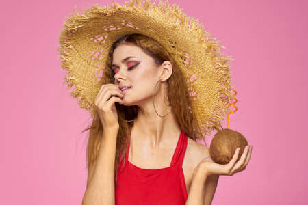 Woman with coconut cocktail in straw hat exotic vacation summer pink background