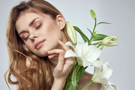 Emotional woman with flowers spring model naked shoulders clear skin