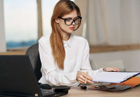 woman secretary in white shirt work desk laptop work emotions
