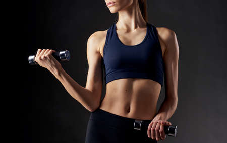 woman with pumped up abdominal muscles holds a dumbbell in her hand on a dark background