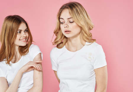 two cheerful girlfriends in white t-shirts lifestyle pink background Imagens