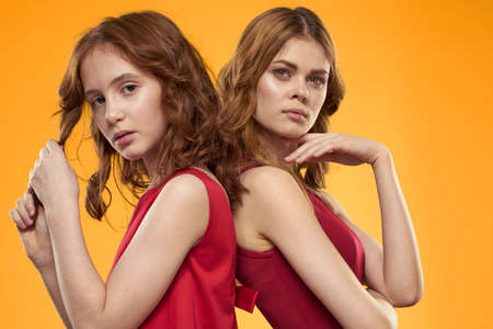 mom and daughter in red dresses communication emotions lifestyle yellow background