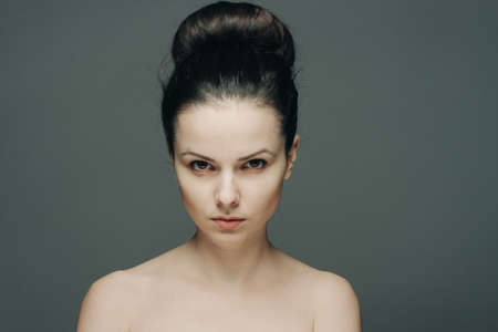 beautiful woman with bare shoulders clear skin collected hair emotions