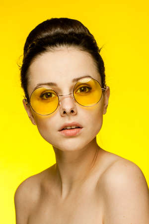 pretty woman with bare shoulders emotions fashionable yellow glasses cropped view