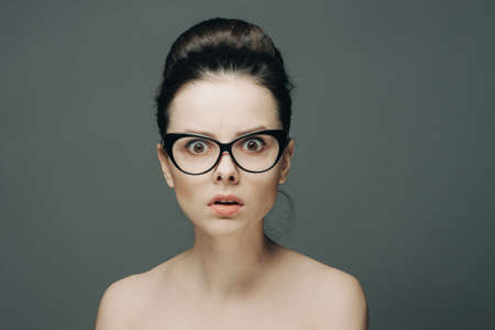 surprised woman with glasses naked shoulders gathered hair gray background Foto de archivo