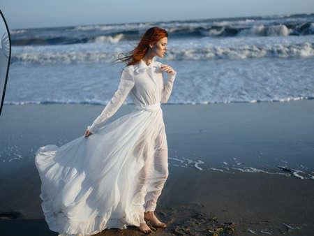 Portrait of a woman in a dress by the ocean on the beach, in full growth Foto de archivo