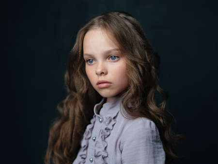 portrait of a beautiful girl in a gray dress on a dark background and curly hair blue eyes Foto de archivo