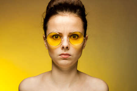 woman with bare shoulders yellow glasses surprised look close-up