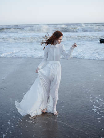 Romantic Woman in White Wedding Dress on the Beach by the Ocean