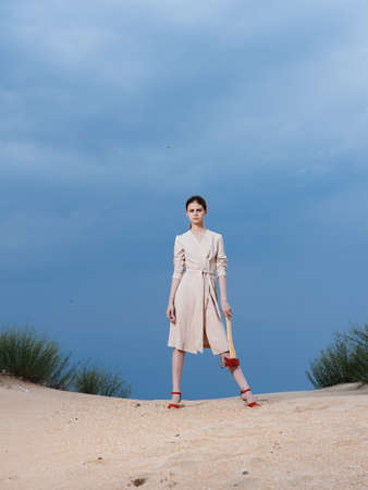 Woman sundress red shoes ax sand nature blue sky Foto de archivo
