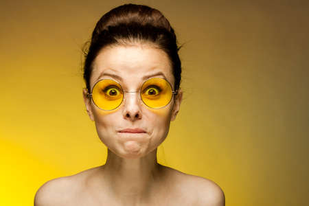 cheerful brunette naked shoulders yellow glasses emotions studio Foto de archivo