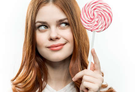 pretty red-haired woman with circle of lollipop in her hands charm passion sweets