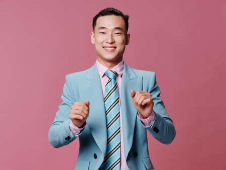 Cheerful man in blue business suit pink background