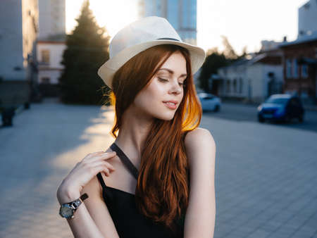 A beautiful woman with red hair in a white hat and in a black dress on the street in the city