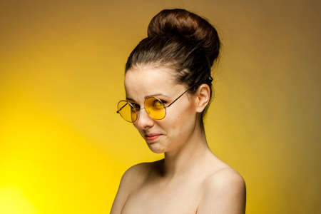 woman in yellow glasses naked shoulders gestures with hands