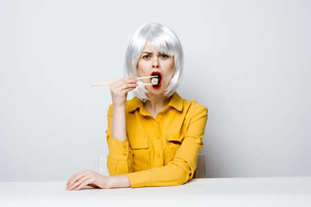 pretty Woman in a white wig sits at a table in a yellow shirt sushi rolls have a snack