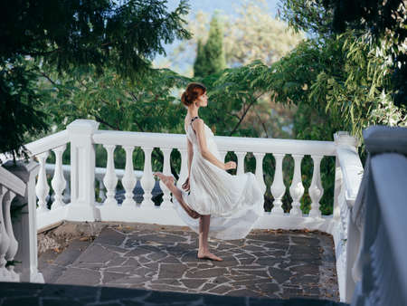 Beautiful woman in white dress traditional greek clothing nature green leaves Foto de archivo