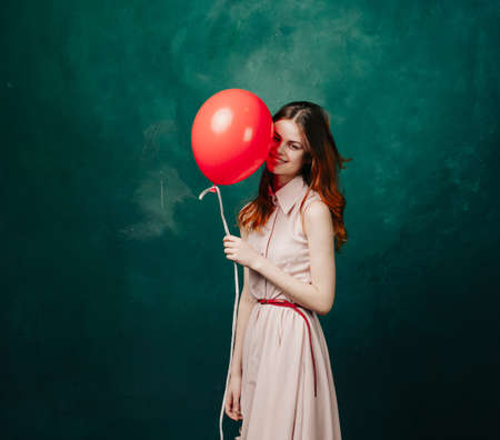 woman on a green background holds a helium balloon in her hand and holidays birthday Foto de archivo
