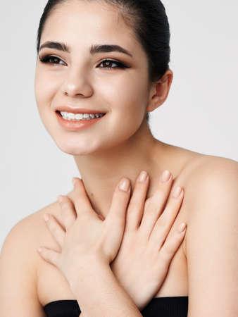 smiling woman face with makeup nude shoulders hands near neck Foto de archivo