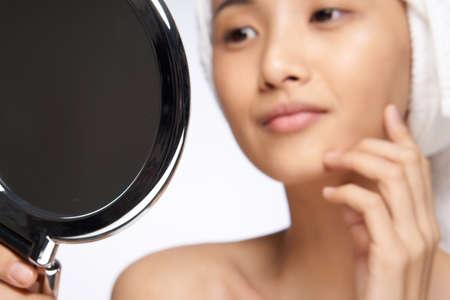pretty woman looking in the mirror healthy skin rejuvenation spa treatments