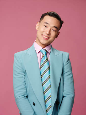 Cheerful man of Asian appearance blue suit self confidence pink background Foto de archivo