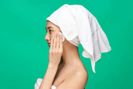 woman with bare shoulders wipes her face but with a cotton pad after make-up Green background Foto de archivo
