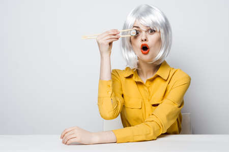pretty woman in white wig eating sushi rolls restaurant