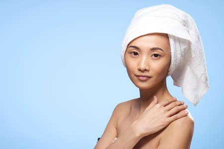 pretty woman asian appearance bare shoulders towel on head spa procedure blue background