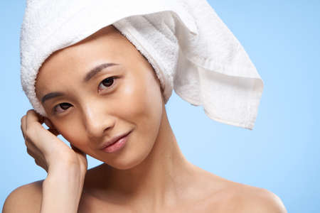 pretty cheerful woman of asian appearance with a towel on her head close-up blue background