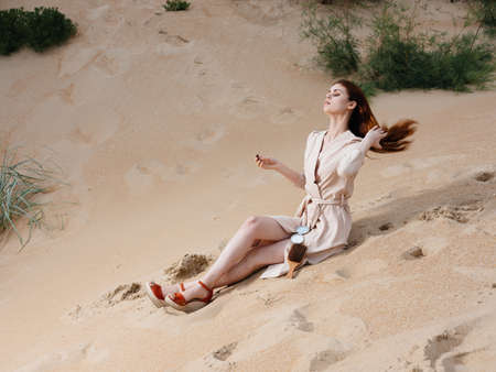 A woman in a light dress and red sandals on the sand on the beach near the sea