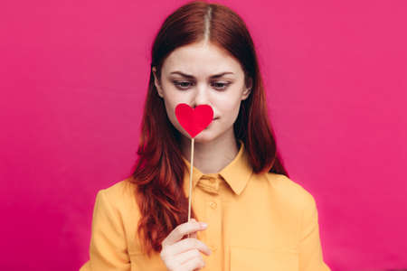 pretty woman in shirt holding heart on stick on pink background Copy Space