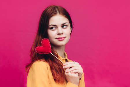 a woman on a pink background holds in her hand a red heart made of fabric Valentines Day