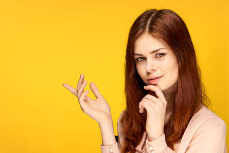 pretty woman gesturing with her hands on yellow background charm