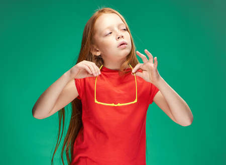 surprised girl with red hair holding glasses in her hands emotions green background school Foto de archivo